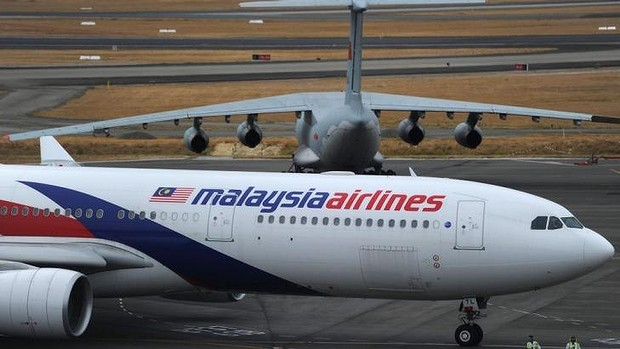 Mystery: A Malaysia Airlines plane prepares to go onto the runway and pass by a stationary Chinese Ilyushin 76 search aircraft (top) at Perth International Airport. Photo: AFP