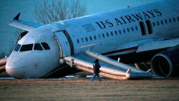 A person walks around a damaged US Airways jet at the end of a runway at the Philadelphia International Airport, Thursday, March 13, 2014, in Philadelphia.