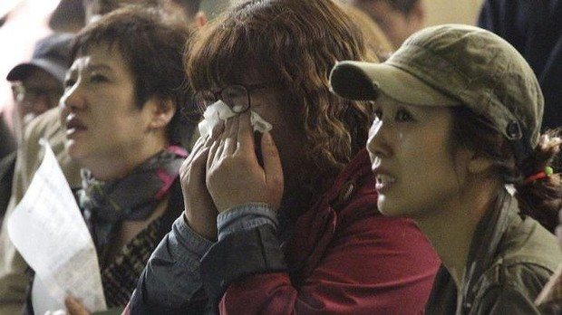 Parents search for their children's names in a list of survivors at Danwon high school in Ansan, South Korea. Photo: AP