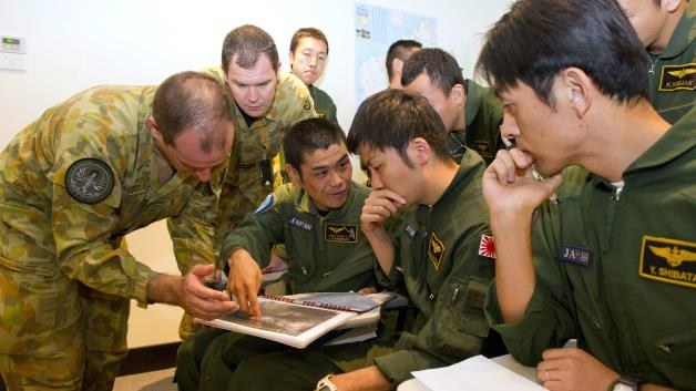 Officers from the Royal Australian Air Force discuss search plans with personnel from the Japan Maritime Self-Defence Force during a pre-flight briefing at RAAF Base Pearce in Perth, Australia, on Tuesday, April 1, 2014.