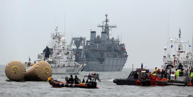 South Korean rescue team members try to search missing passengers of the sunken ferry Sewol near buoys which were installed to mark the area in the water off the southern coast near Jindo, South Korea, April 19, 2014.