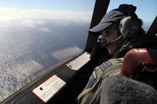 Royal New Zealand Air Force captain, Wing Commander Rob Shearer, looks out from the cockpit of his search aircraft while flying over the southern Indian Ocean on Monday, March 31, 2014.