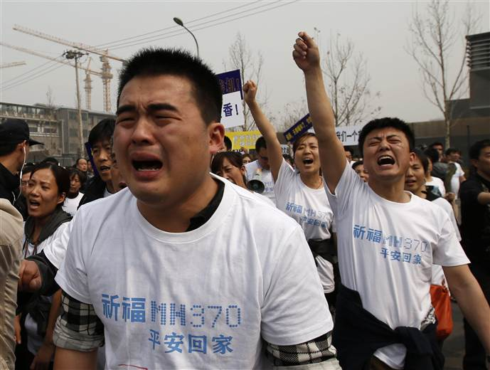 Family members of passengers onboard Malaysia Airlines MH370 cry as they shout slogans during a protest in front of the Malaysian Embassy in Beijing on Tuesday.